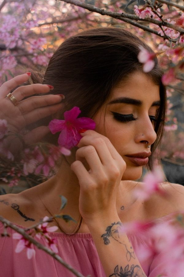 Lady placing a pink flower behind her ear