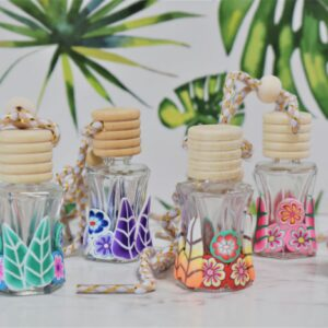 Mini Glass Diffuser Bottles with colourful clay flowers around and wooden lids