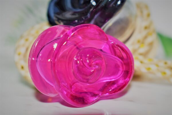 Close up of a glass pink rose diffuser bottle