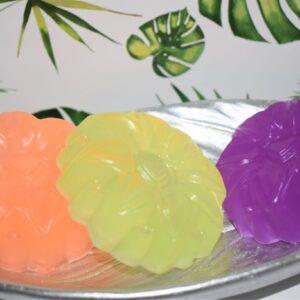 3 flower shaped soaps of orange, lemon and purple
