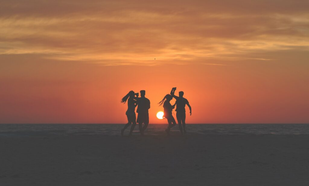 people dancing on the beach in the sunrise