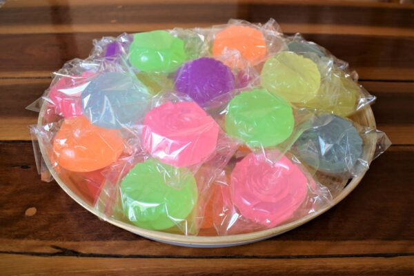 A bowl of colourful flower shaped soap favours