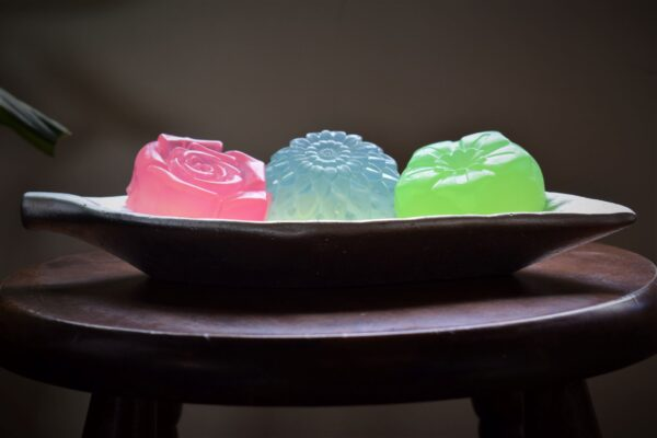 A rose soap, a blue soap and a green soap lined up in a tray