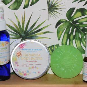 "Bottle of ""Neroli water, palmarosa body butter"" a green soap and ""meadow facial serum"""