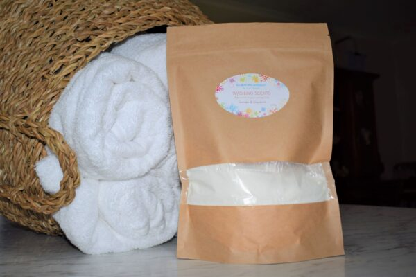 Packet of 'washing scents lavender and chamomile' near towels in basket